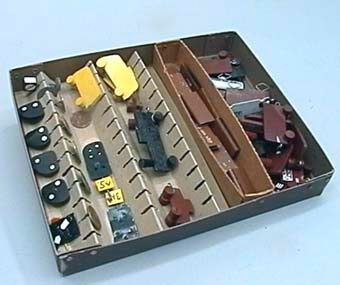 Spel eller utbildningsmateriel i ask.  Spelet består av 2 ånglok, 2 lokomotorer, 2 ellok, 2 rälsbussar, 1 motordressin, 11 godsvagnar, 1 öppen - stållastad vagn, 1 cisternvagn, 20 vikta plåtar (För att kunna ändra text på godsvagnarna till t.ex; KLOR, Expl. vara II kl), 8 st dvärgsignaler, 1 markör för C-fordon.  Allt rullande materiel har krokar fram och bak som koppel.