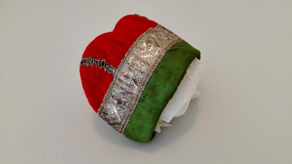 1 barnehue.  Av rødt klæde, kantet med grønt tøi og sølvlidser, foret med blomstret tøi. Gave fra Ingebrigt Andersen Rislag, Vik.