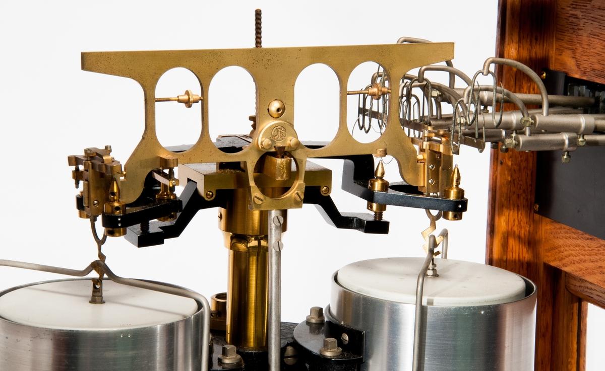"""Våg som användes för precisionsvägande. Vågen ser ut som ett glasskåp. Har texten """"Sartorius Werke AG Göttingen"""" nära toppen. Vågarna kan tas av och har en guldaktig färg."""