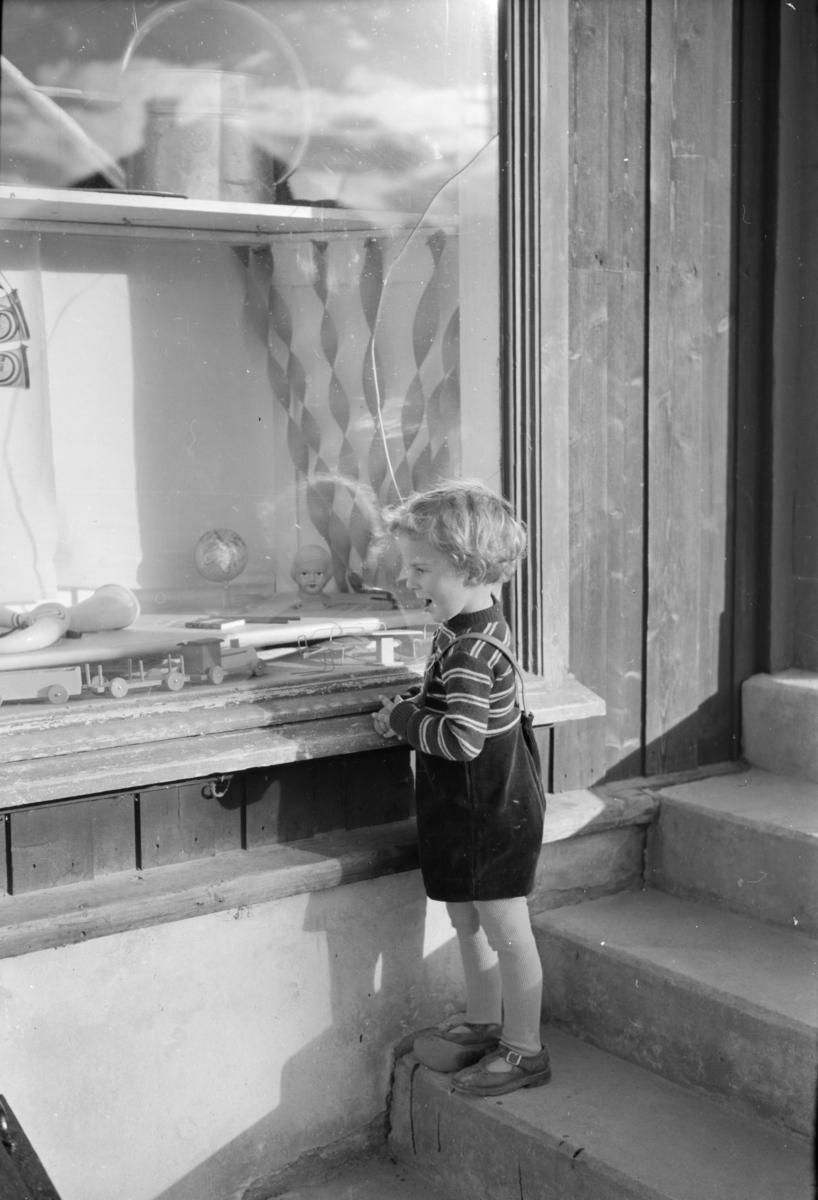 Liten gutt ser på utstillingsvindu med blant annet et tog i tre