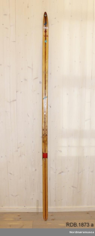 Avsmalende, jevnbred ski med liten bue. Bøy uten tupp. Tilspisset brettende. Dekorert med ei brun stripe på trehvit bunn.