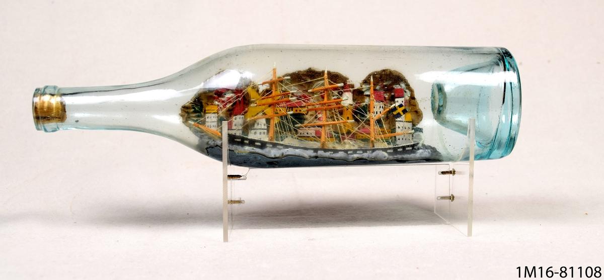 Flaskskepp. Flaskan är av glas och vilar i en ställning av plexiglas och metallskruvar. I bakgrunden en stad.
