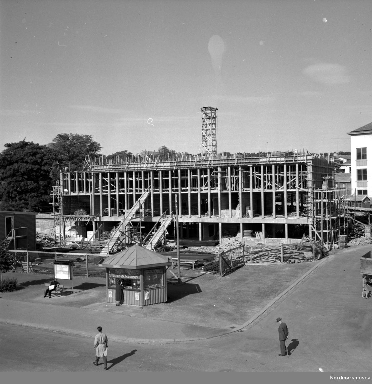 Foto fra byggeplassen til Folkets hus på Kongens plass på Kirkelandet i Kristiansund. Bildet kan trolig dateres til omkring 1958. Fotograf er Nils Williams. Fra Nordmøre museums fotosamlinger.