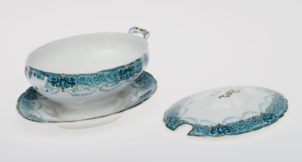 """To identiske ovale sausenebb med lokk i steintøy med glasur. Foten er fastmontert på et ovalt fat. Det er påtrykt mønster på skål, fat og lokk. Det er blågrønne bladranker ytterst mot kantene og hengende blomsterranker. Blomsterbånd langs kantene er støpt i godset. Det er håndmalt med gull på bladrankene, på håndtakene og på toppen av lokkene. Lokkene har et hull i den ene siden for plassering av øse. De tilhører et større servise (se relaterte objekter) som heter Verona. Det er stempel på undersiden av fatene, se """"Påført tekst/merker""""."""