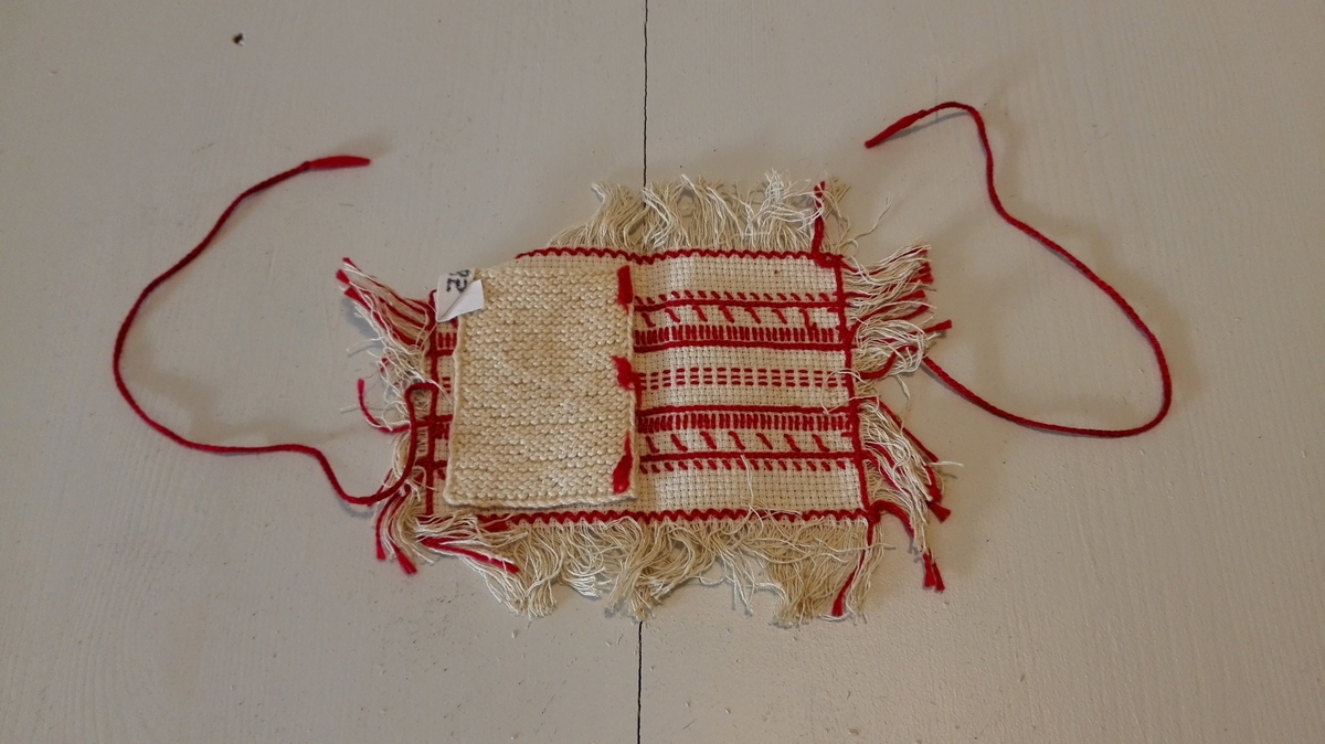 Form: Rektangulær. 1 nålepute.  Innlagd strikka lapp til nåler. Bretta og knytt/lukka med hekla band.