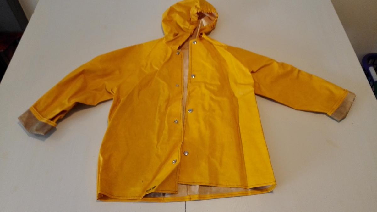 Form: Halvsid med hette. 1 regnjakke.  Halvsid med hette og raglanermer. Forknappa med trykk-knappar. Uten lommer.