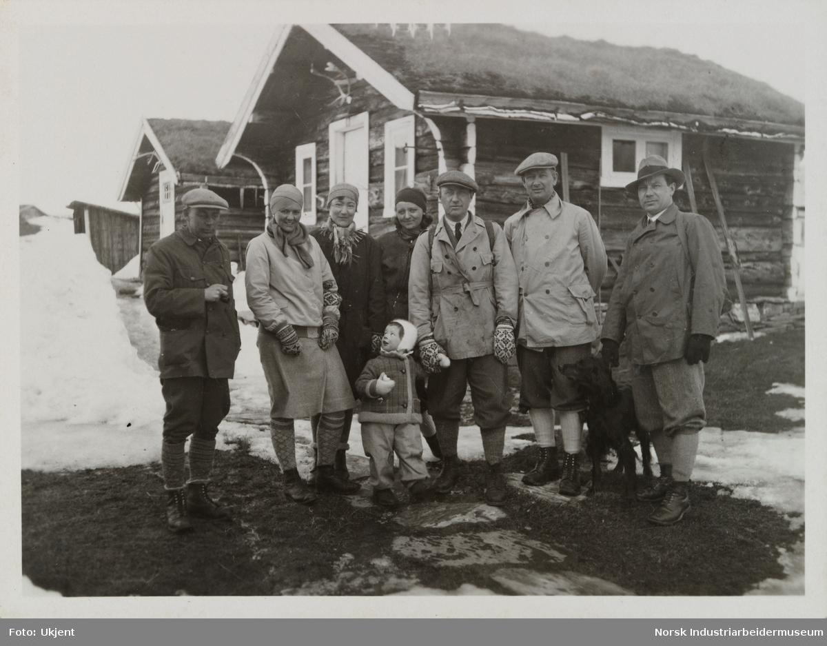 En gruppe med mennesker utendørs ved hytteområde. Fire menn, tre damer, et barn og en hund.