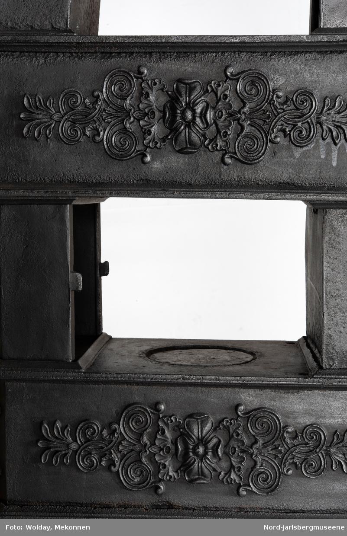 4 etasjer.  Røykkamrene er sekskantete, med planteornamentikk. Brennkammerets sideplater dekoret med liggende plante- og palmettornamenter. Askeplate avrundet rektangulær.  Står på trekrakk, sortmalt (slitt)) Original?