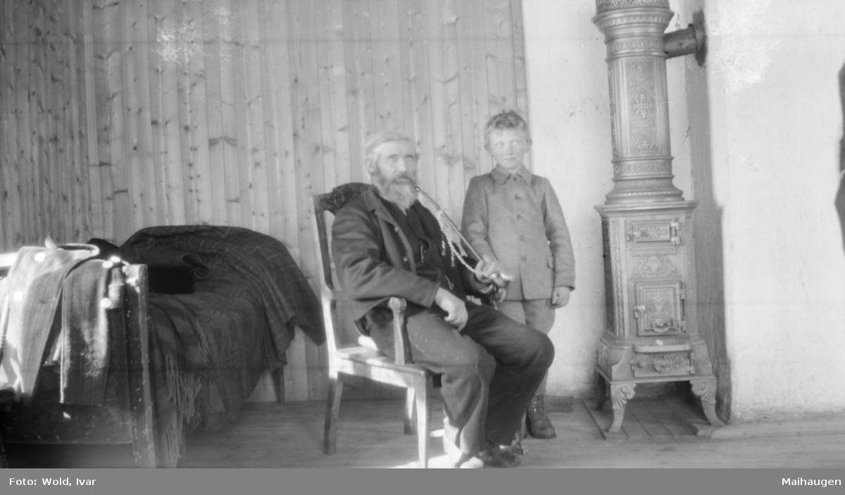 Eldre mann med krokpipe og gutt, innen ved en rund - muligens på Linjordet i Østre Gausdal