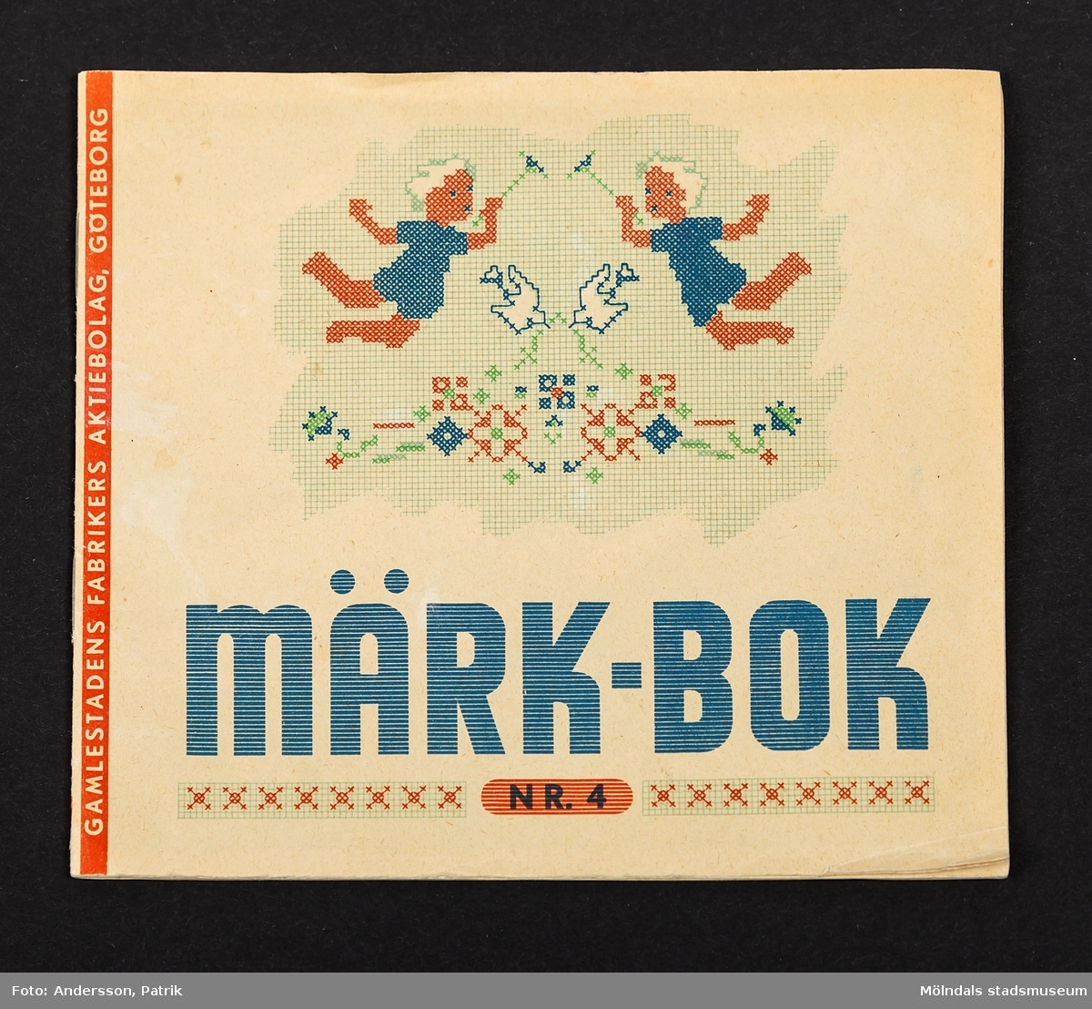 Märk-bok nr 4, från Gamlestadens fabriker Aktiebolag (reklamhäfte).  Vit framsida med en ilustration i form av mönster till ett korstyngsbroderi. Häftets titel är tryckt i blått. Häftet innehåller mönster och mallar för broderi, tänkta att smycka lakan och örngott.