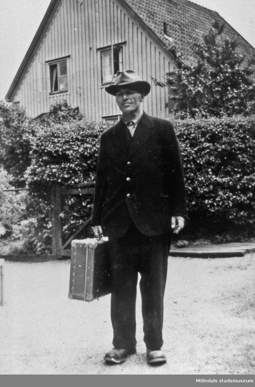 Ålderdomshemmet Kärra Hökegård i Kärra, Mölndal, år 1951. Karlsson med väskan. Någon påstod att han var född på hemmet och bott där hela sitt liv. När han kom till Lackarebäck fortsatte han att gå ärenden. Sven Olof Olsson berättar att när Karlsson kom in på hans tjänsterum på Stadshuset lämnade han ett brev men det gick inte att tala med honom. I bakgrunden ses föreståndarbostaden som blev arrendatorbostad när gården arrenderades ut till Ivar Brogren. AF 8:27.