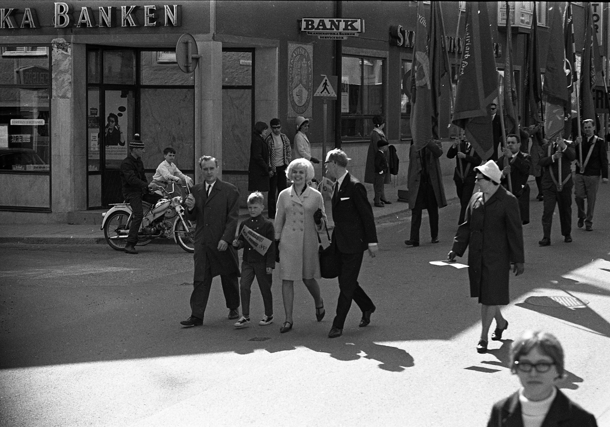1:a majtåg. Demonstration på Nygatan. Främsta raden, från vänster: Bertil Karlsson (ordförande i stadsfullmäktige) med son, Berit Oscarsson (ungdomstalare från Sveriges Socialdemokratiska Ungdomsförbund), Åke Zetterberg (pastor och ordförande i Broderskapsrörelsen) samt Anna-Lisa Isaksson (ordförande i Fackens CentralOrganisation) Män med fanor. Skandinaviska Banken i bakgrunden.