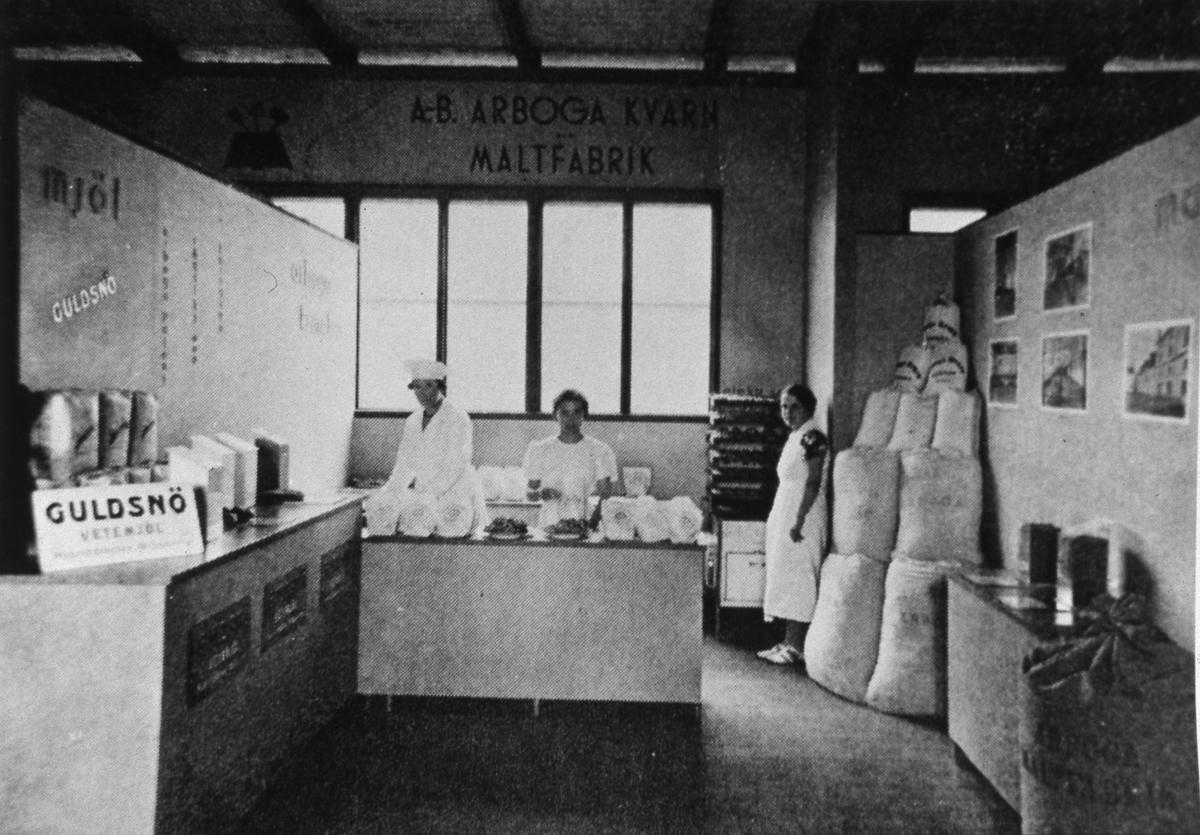 Arboga Kvarn och Maltfabriks monter på Arbogautställningen. Tre kvinnor arbetar i montern. Där finns mjölsäckar staplade i hörnet och reklam för mjölmärket Guldsnö.