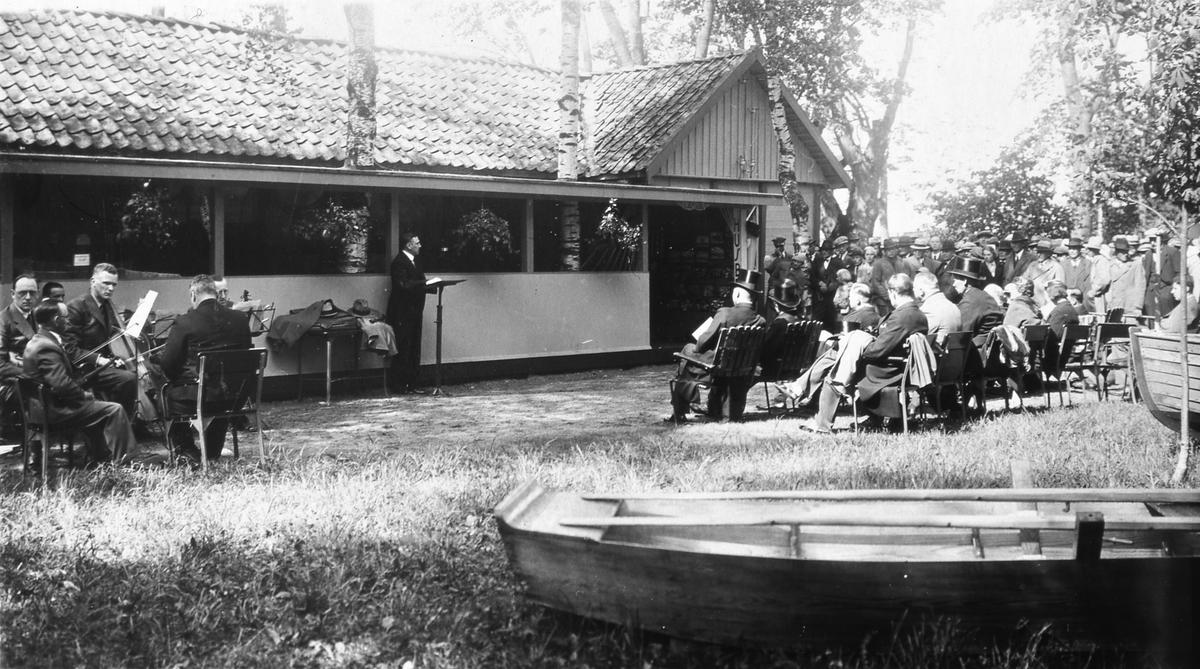 Invigning av fiskeriutställningen. Den visas vid kägelbanan. En man talar. Bredvid sig har han en stråkorkester. Publiken sitter i trädgårdsmöbler. I förgrunden ligger en roddbåt. Arbogautställningen pågår i staden.