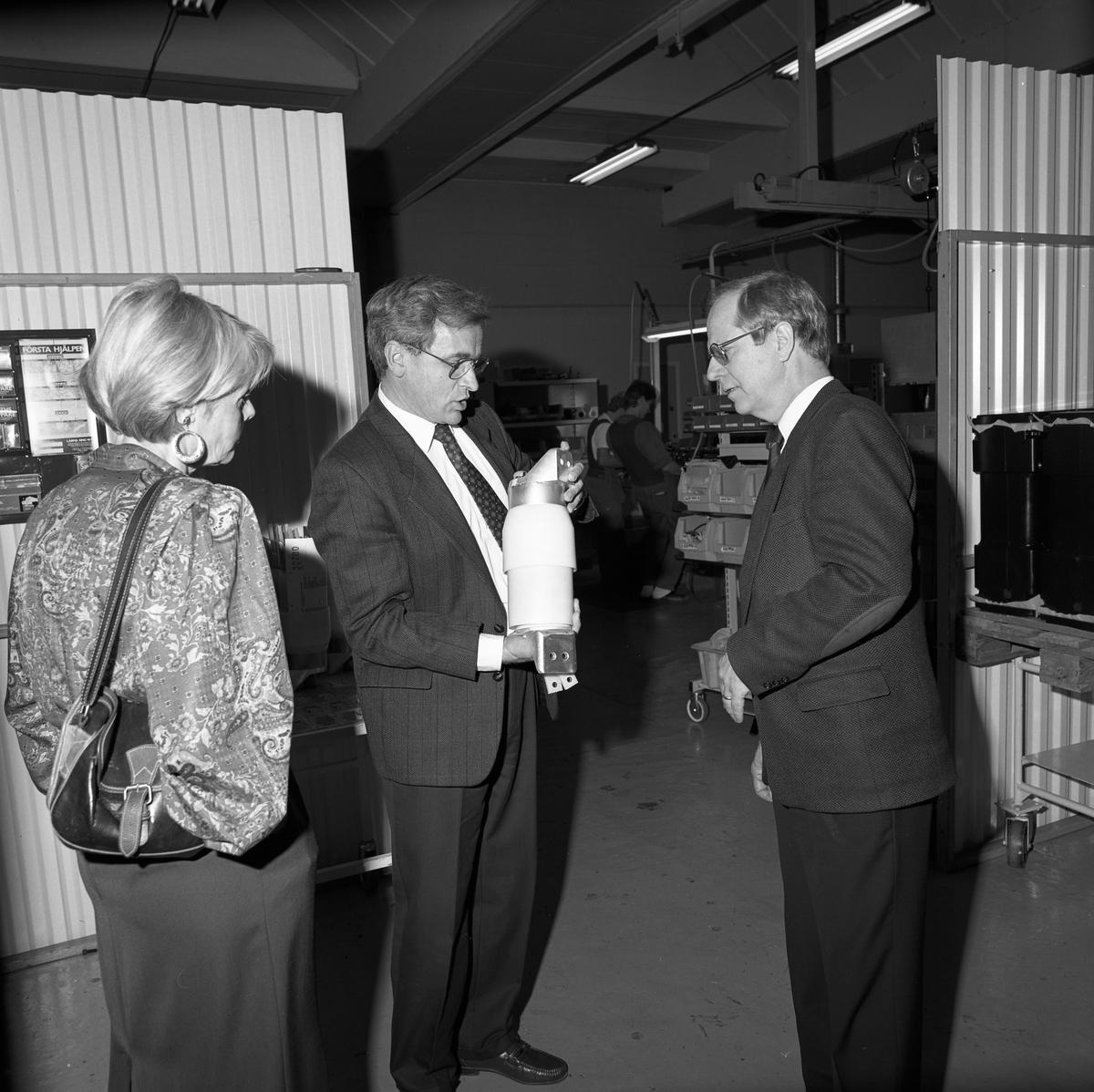 Landshövding Jan Rydh (till höger) besöker ASEA Brown Boveri i Västerås. Okänd kvinna till vänster. De studerar en pjäs i industrilokalen. Med på besöket är även Per-Olov Nilsson och Elsy Harrysson, som syns på andra bilder i serien.