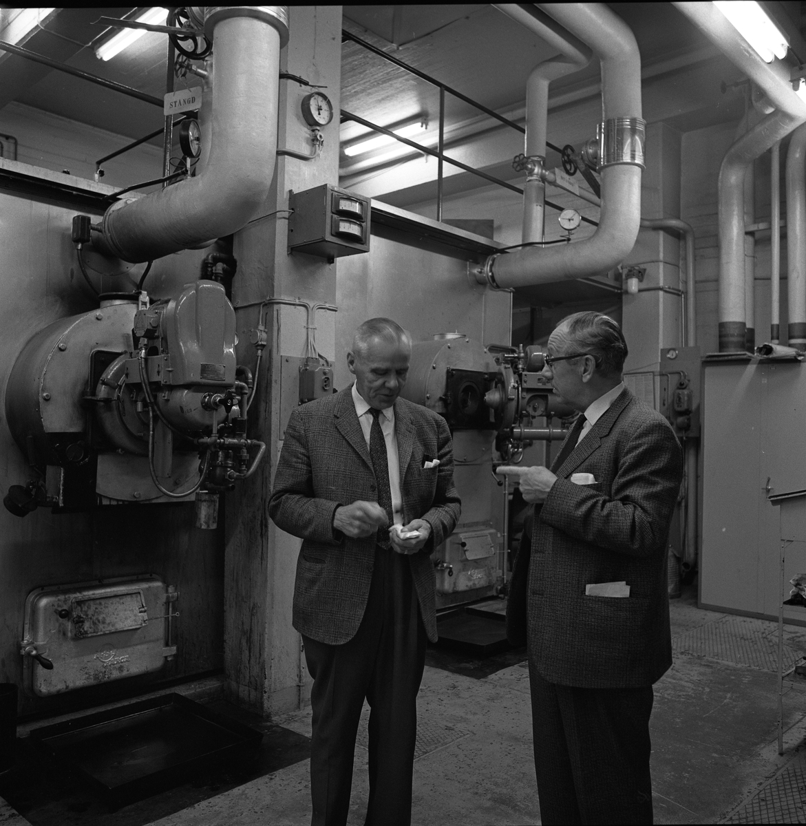 Alf Hedlund, maskinmästare på Centrala Verkstaden Arboga (till vänster). Den andre mannen är okänd. De är båda klädda i kostrym och befinner sig i verkstadsmiljö.