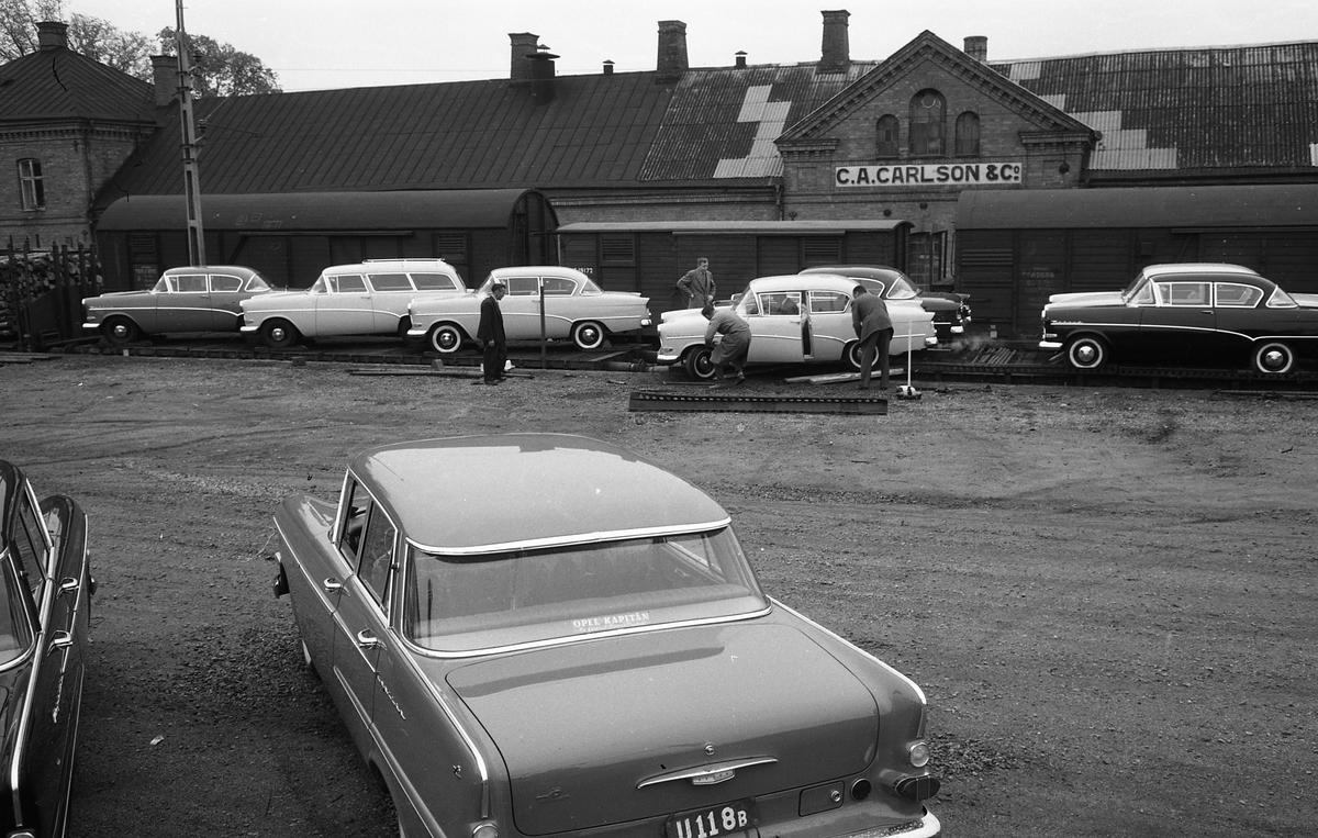 Flera bilar, av märket Opel Kapitan, anländer på järnvägsvagnar. Några män lastar av bilarna. Bilarna ska vara på plats hos Arboga Bil AB till invigningen.  Bakom järnvägsspåren ligger C.A Carlsson & Co