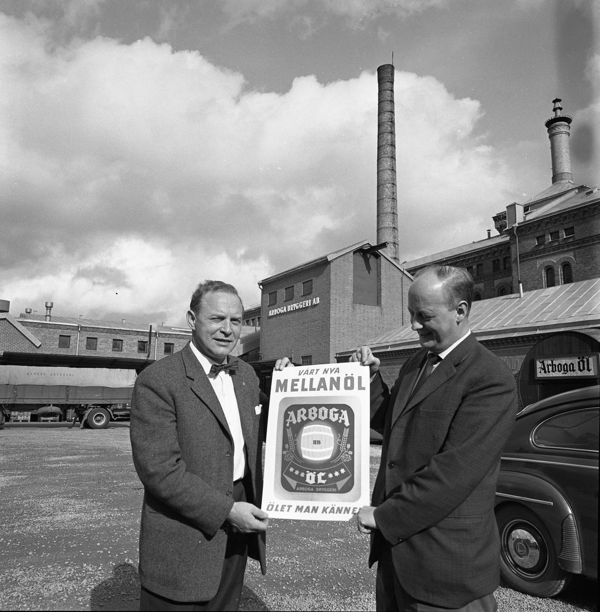 """Arboga Bryggeri. Permiär för mellanölet. Två kavajklädda män står utanför bryggeriet. De håller i en reklamskylt med texten """"Vårt nya mellanöl, Arboga öl, ölet man känner"""". Mannen till vänster är Helge E Carlsson. Mannen till höger är Ture Anderberg, bryggmästare.  Anläggningen var färdigbyggd 1899 och verksamheten startade 1 november samma år. 24 oktober 1980 tappades det sista ölet, på bryggeriet. Märket var Dart. Läs om Arboga Bryggeri i hembygdsföreningen Arboga Minnes årsbok 1981"""
