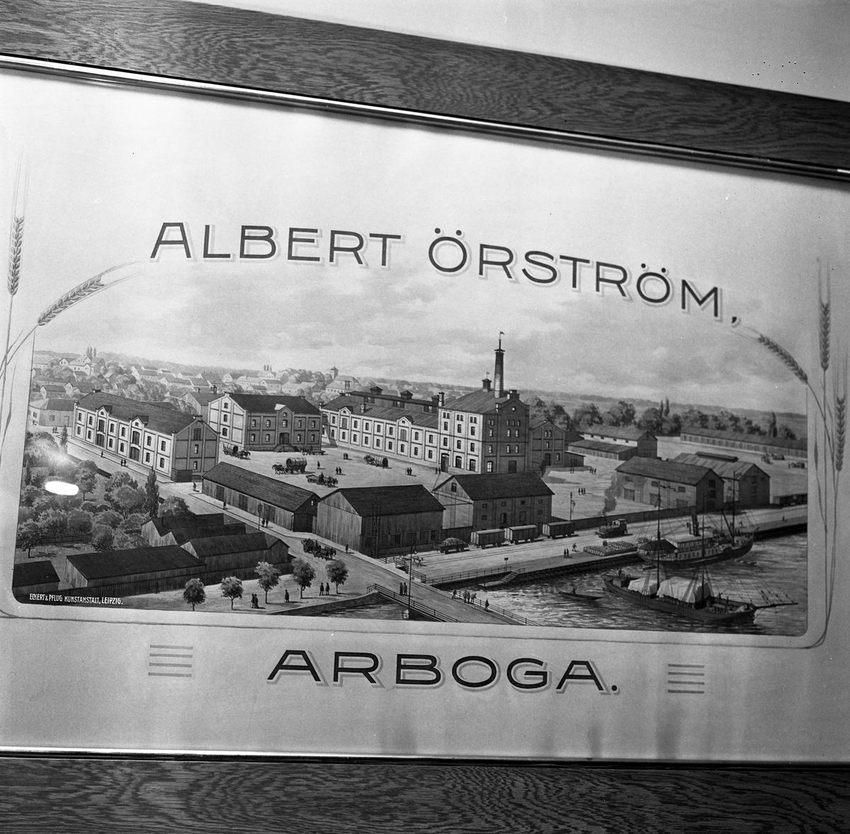 Arboga Kvarn och Maltfabrik, exteriör. En tavla, föreställande fabriken, hamnmagasinen, järnvägen och båtar i hamnen. Bilden omges av texten Albert Örström Arboga och några veteax. Bilden är framtagen av Kunstanstalt Leipzig, enligt text i tavlans nedre vänstra hörn.  Det som kom att bli Arboga Kvarn och Maltfabrik anlades 1821 av Jonas Örström. Grosshandlare Albert Örström övertog rörelsen 1877. Han startade här en elektrisk kvarn, 1915, när verksamheten vid kvarnen i Höjen lades ner. Vetemjöl av märket Guldsnö framställdes här.  Kvarnrörelsen upphörde 1967 och maltproduktionen upphörde 1972.  Läs om Arboga Kvarn och Maltfabrik: Hembygdsföreningen Arboga Minnes årsböcker från 1979 och 1999 Reinhold Carlssons bok Arboga objektivt sett