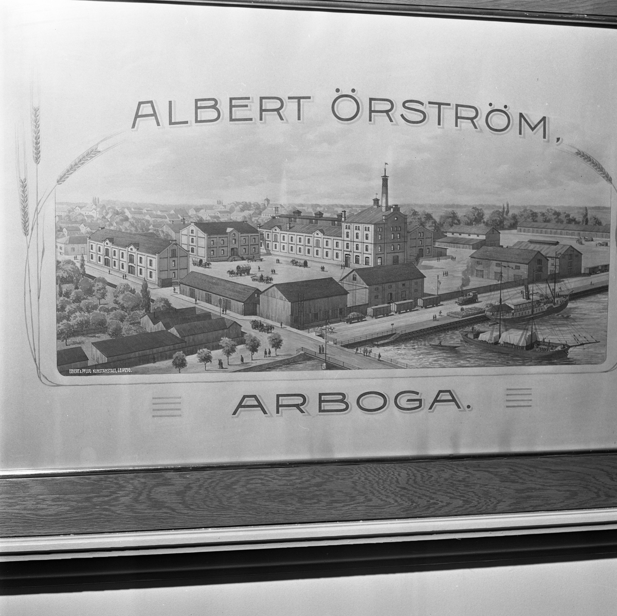 Arboga Kvarn och Maltfabrik, exteriör. En tavla, föreställande fabriken, hamnmagasinen, järnvägen och båtar i hamnen. Motivet omges av texten Albert Örström Arboga och dekoreras med några veteax. Bilden är framtagen av Kunstanstalt Leipzig, enligt text i tavlans nedre vänstra hörn.  Det som kom att bli Arboga Kvarn och Maltfabrik anlades 1821 av Jonas Örström. Grosshandlare Albert Örström övertog rörelsen 1877. Han startade här en elektrisk kvarn 1915, när verksamheten vid kvarnen i Höjen lades ner. Vetemjöl av märket Guldsnö producerades här.  Kvarnrörelsen upphörde 1967 medan maltproduktionen pågick fram till 1972.  Läs om Arboga Kvarn och Maltfabrik: Hembygdsföreningen Arboga Minnes årsböcker från 1979 och 1999 Reinhold Carlssons bok Arboga objektivt sett