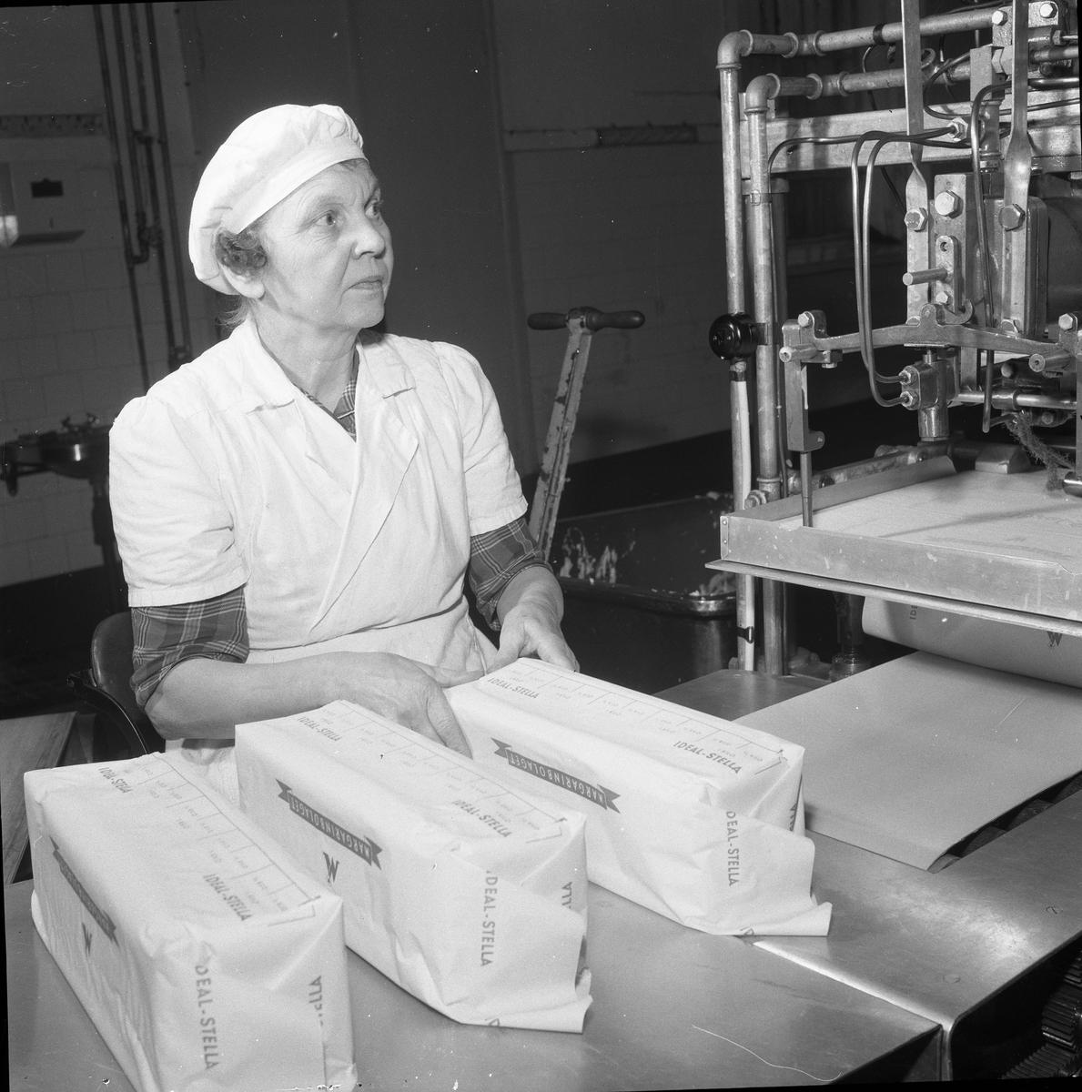 Arboga Margarinfabrik, interiör.  Edit Persson började sin anställning 1911, då var hon 14 år. Arbetet var tungt och mycket gjordes för hand. Arbetstiden varade från klockan 06.00 till 18.00. Edit arbetade i fabriken tills den lades ner, 1960. Det blev 49 år på samma arbetsplats.  Läs om Arboga Margarinfabrik i Arboga Minnes årsbok 1978 och Reinhold Carlssons bok Arboga objektivt sett.