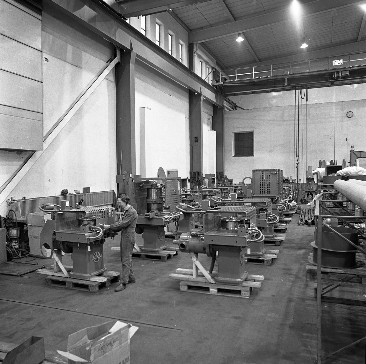 Arboga Mekaniska Verkstad, interiör från maskinverkstad och monteringsavdelning. Industrilokal med högt i tak, traverser och maskiner i rader. En man arbetar vid en maskin.  25 september 1856 fick AB Arboga Mekaniska Verkstad rättigheter att anlägga järngjuteri och mekanisk verkstad. Verksamheten startade 1858. Meken var först i landet med att installera en elektrisk motor för drift av verktygsmaskiner vid en taktransmission (1887).  Gjuteriet lades ner 1967. Den mekaniska verkstaden lades ner på 1980-talet. Läs om Meken i Hembygdsföreningen Arboga Minnes årsbok från 1982.
