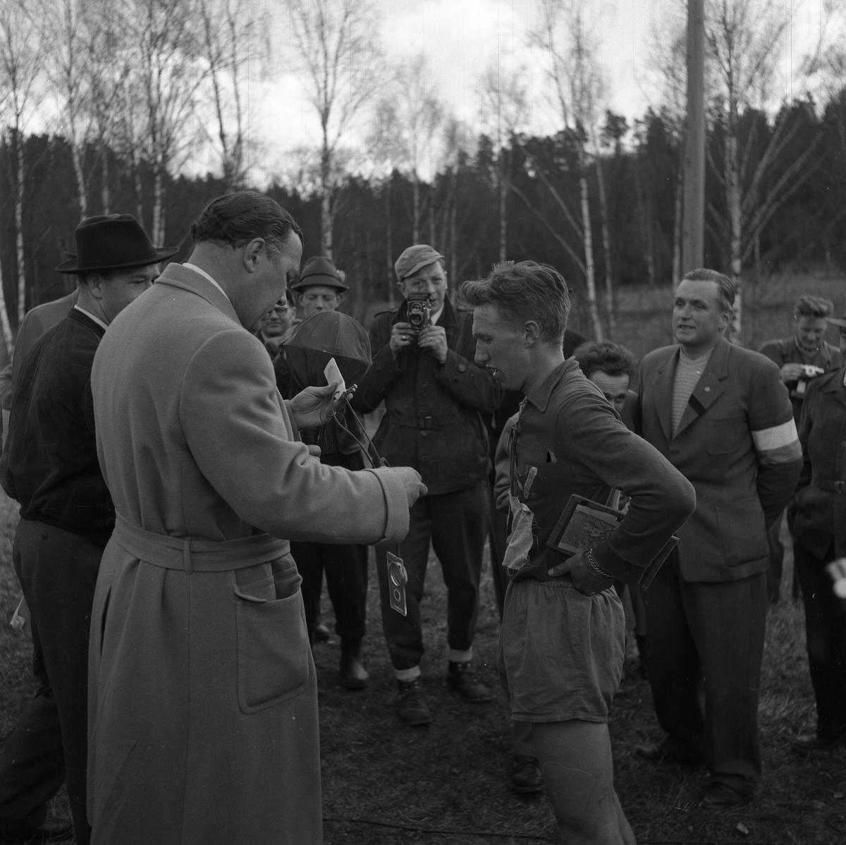 """Arboga Orienteringsklubb har vunnit tiomilaorienteringen. Lennart Öberg (med kartan i handen) samtalar med Prins Bertil medan fotografer och funktionärer ser på. Lennart Hyland (i mörk hatt) väntar på att få en intervju i radio. Prins Bertil håller i kompassen.  Starten gick i Malmköping och målgången skedde i Bränninge, Södertälje.  Bilder, från detta tillfälle, finns i Reinhold Carlssons bok """"Arboga objektivt sett""""."""