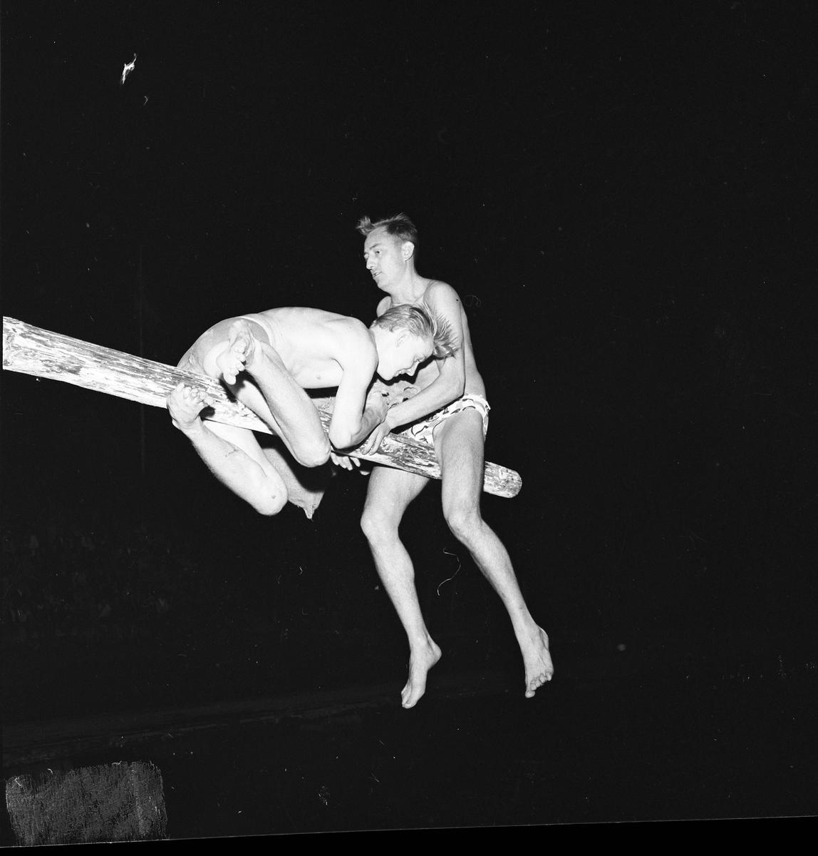 Arboga SimSällskap arrangerar eldfest vid Villagatsbadet Två män, iklädda badbyxor, sitter på en bom / stång över vattnet. De försöker slå ner varandra med var sin säck. I mörkret, nere till vänster, anas publiken.
