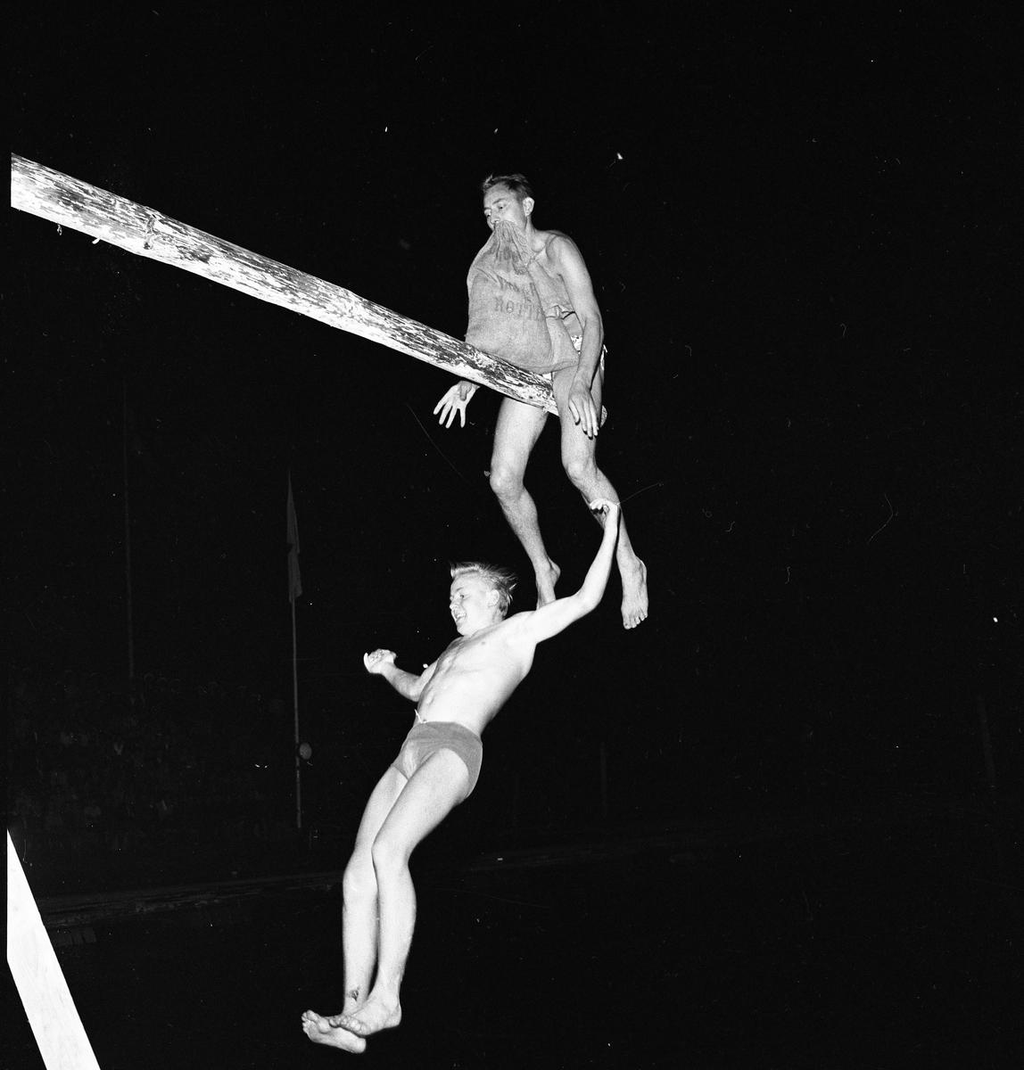 Arboga Simsällskap arrangerar Eldfest vid Villagatsbadet. Två män, iklädda badbyxor, har suttit på en bom / stång över vattnet. De har försökt slå ner varandra med var sin säck. Nu har den ene vunnit och den andre faller ner mot vattnet. Publiken anas till vänster i bild.