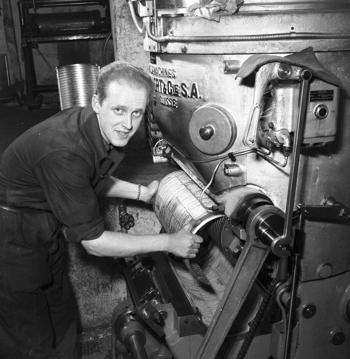 Arboga Tidning, personal och interiör. En man, med uppkavlade skjortärmar, arbetar vid tryckpressen.