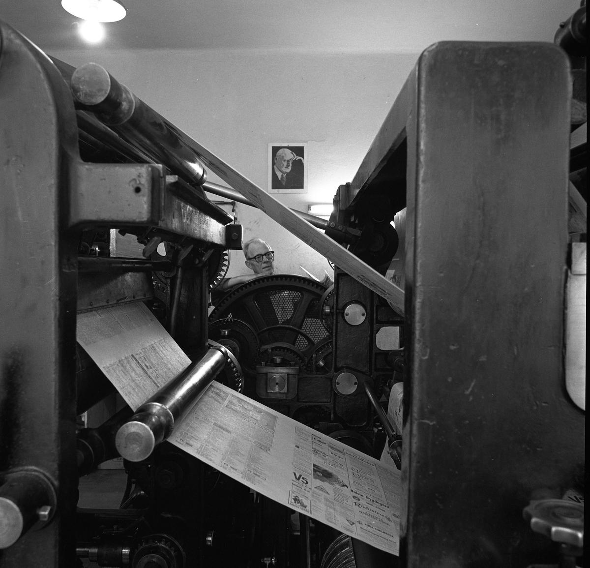 Arboga Tidning, personal och interiör. Tryckeriet. En man arbetar vid tryckpressen. Tryckta tidningssidor rullar mellan valsarna medan mannen kontrollerar maskinen.
