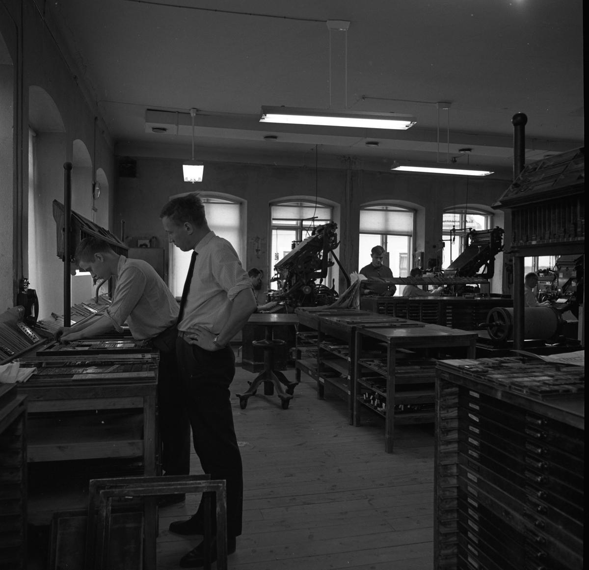 Arboga Tidning, personal och interiör. Flera män arbetar i lokalen. Mannen närmast fotografen bygger ens tidningssida medan en annan man ser på. Stora maskiner står i andra änden av rummet. Rummet har höga fönster och trägolv.