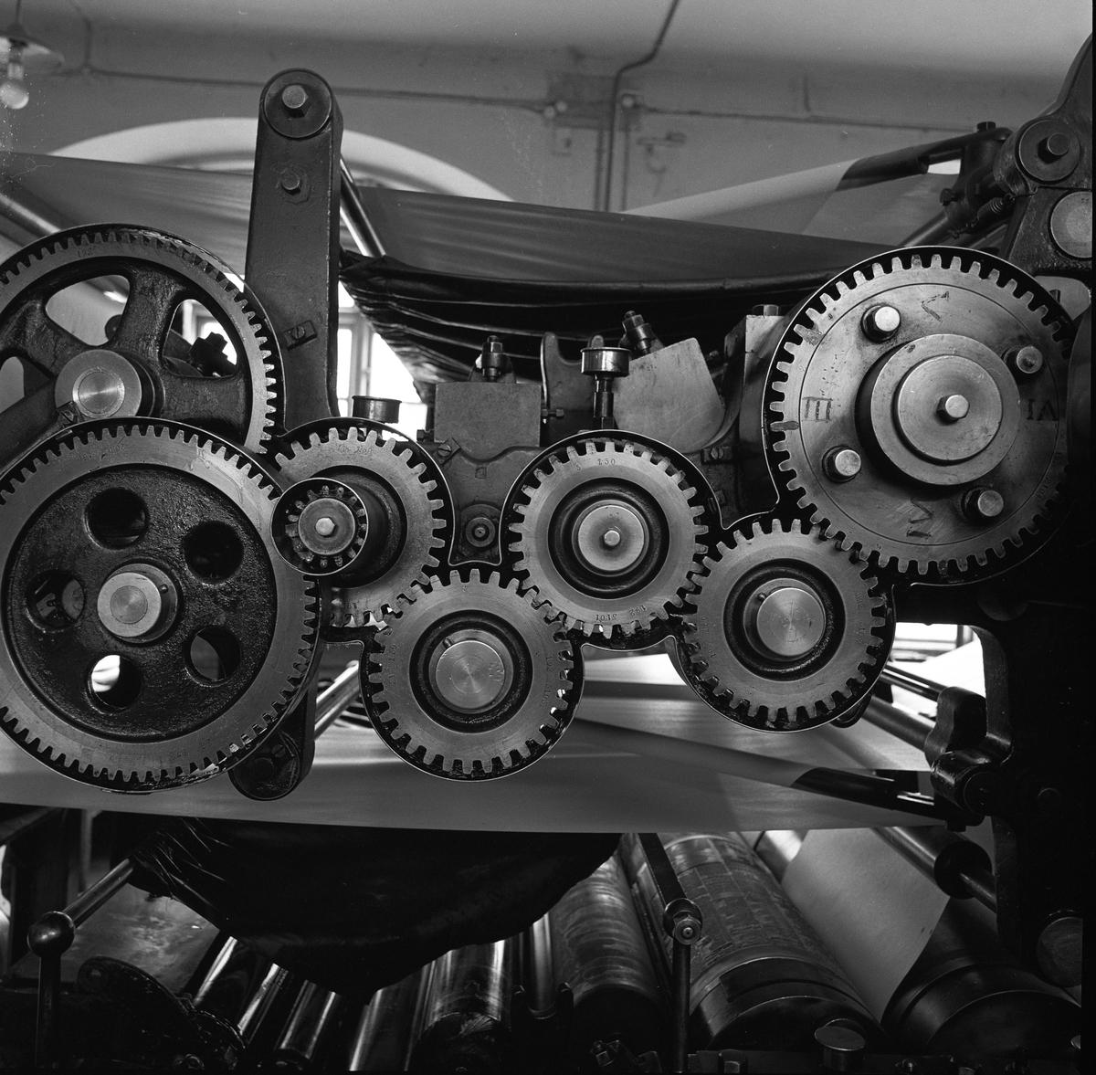Arboga Tidning, interiör. Del av tryckpress. Kugghjul i närbild. Tidningspapperet löper upptill och nertill i bild.