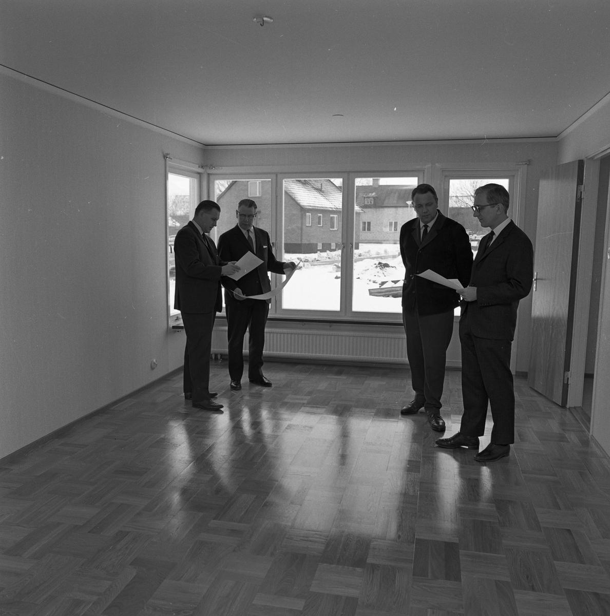 Arbogavillan lll, interiör. På parkettgolvet, i det tomma vardagsrummet, står fyra herrar och diskuterar. De håller i papper, möjligen ritningar.  Hildning Lund, från Byggnadsfirma Lund, är nummer två från vänster. Nummer tre, från vänster, är Norberg. Han är verkmästare hos Lund. Nummer fyra, är Hilding Karnéus, från Arboga Sparbank.
