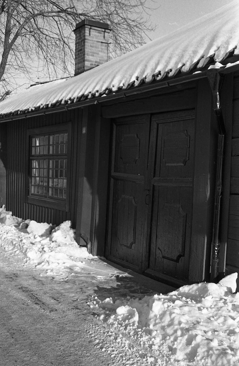 Del av ett boningshus på Ahllöfsgatan. Huset har dubbeldörr och spröjsat fönster. Snön ligger på taket och det är snödrivor på var sida om porten. Porten har ett handtag och en stor nyckel i låset. Enligt skylten vid dörren är gatnumret 13.