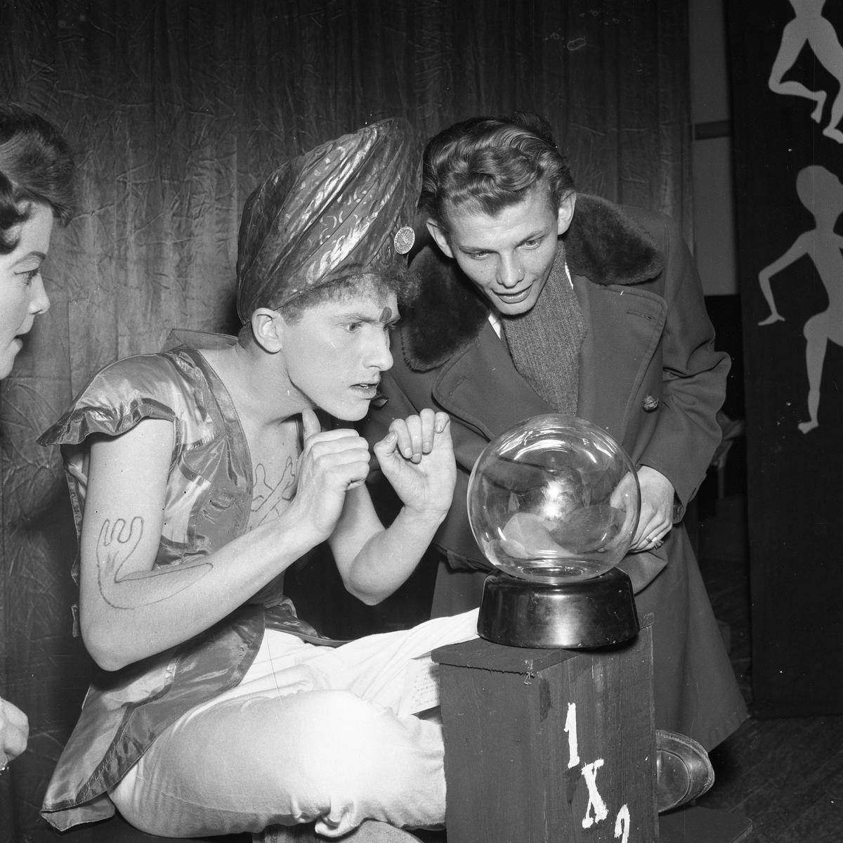 Arbogarevyns medlemmar spelar upp sin Jubileumsrevy. Larz-Thure Ljungdahl, iklädd turban, skådar i sin kristallkula. Mats Torstensson tittar intresserat på.