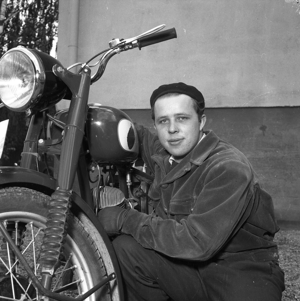 Arbogas Stjärnknutte Ung man som sitter på huk vid en motorcykel. Mannen har basker, jacka och handskar.