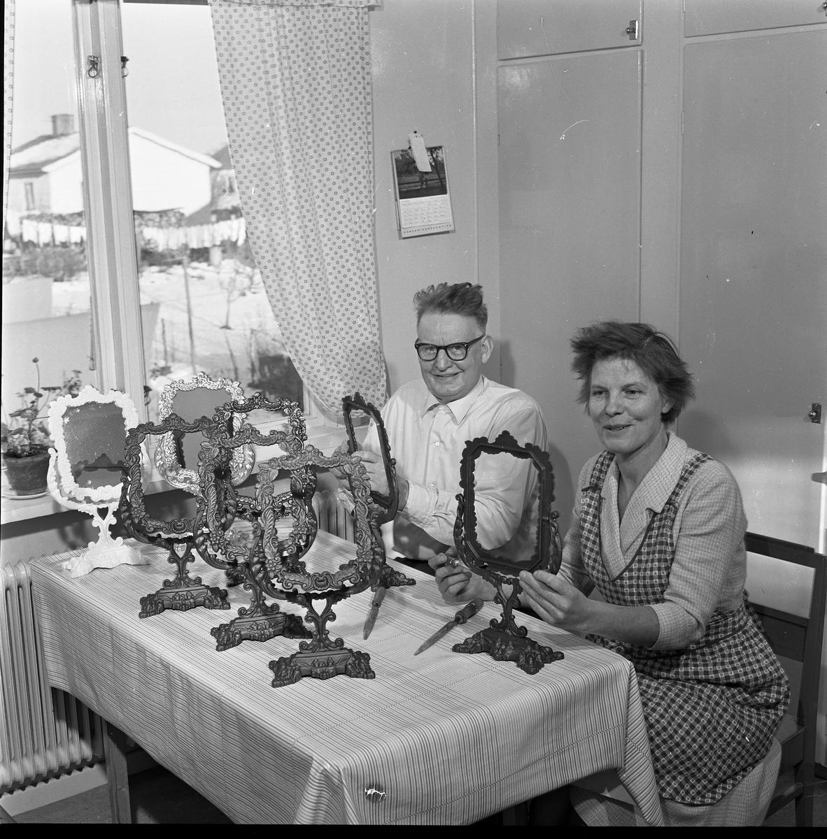 Börjesson tillverkar Arbogaspegel Ett par sitter vid köksbordet. De har spegelramar uppställda på bordet. Kvinnan har förkläde på sig. På väggen hänger en almanacka. Genom fönstret syns villor.