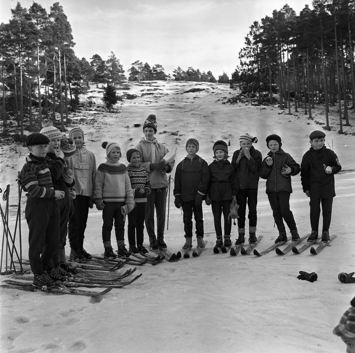 Barnskidskolan har avslutning. Elva barn och en lärare är uppställda nedanför backen. De har längdskidor på sig medan stavarna är satta i snön. De är klädda i stickade tröjor och mössor eller i anorack. De har fått var sitt äpple.