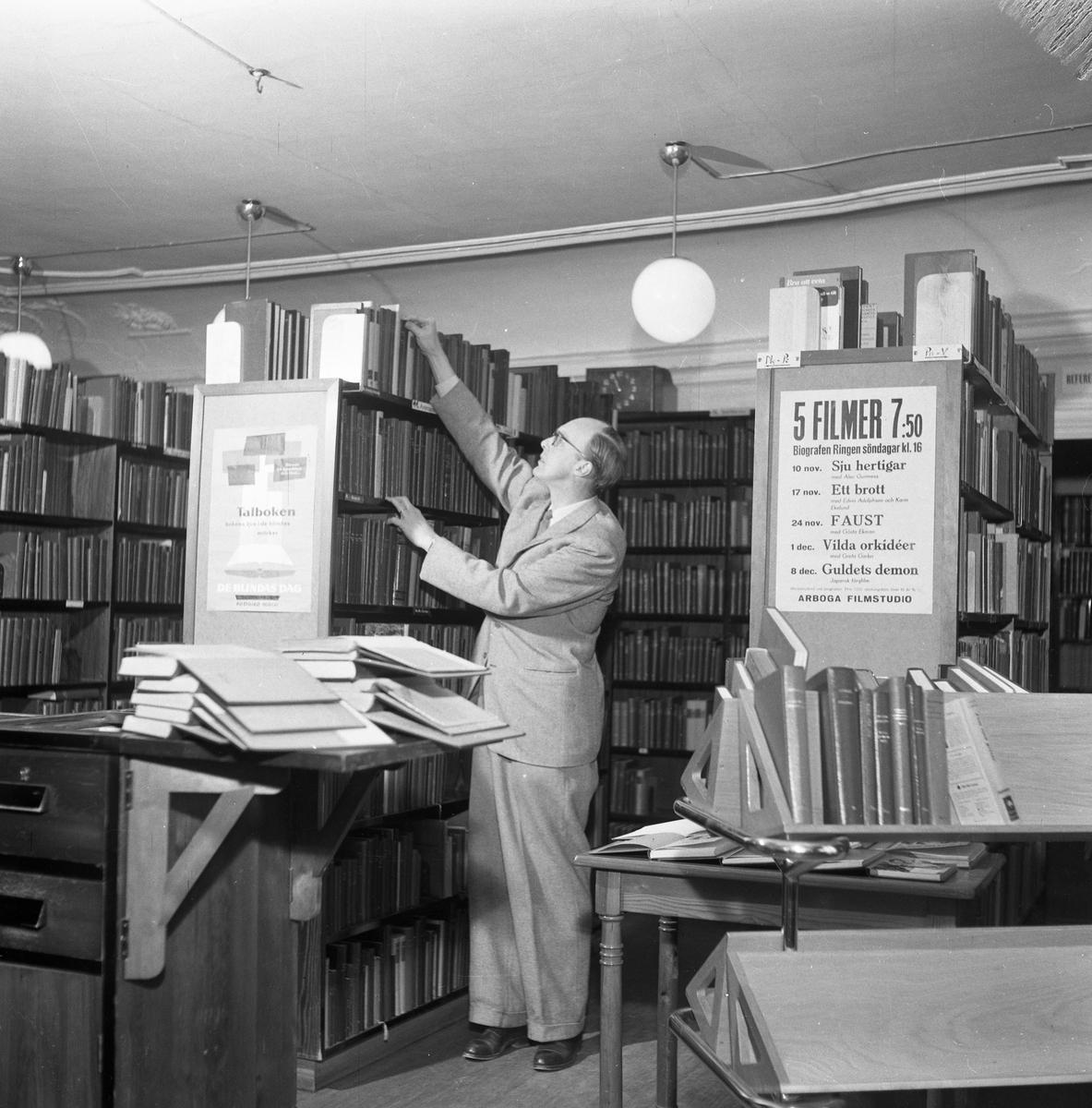 Bibliotekarie Östen Bengtsson. Biblioteket ligger på Nygatan (i gamla Gästis). Kostymklädd man som sätter upp böcker i bokhylla, omgiven av bokhyllor.