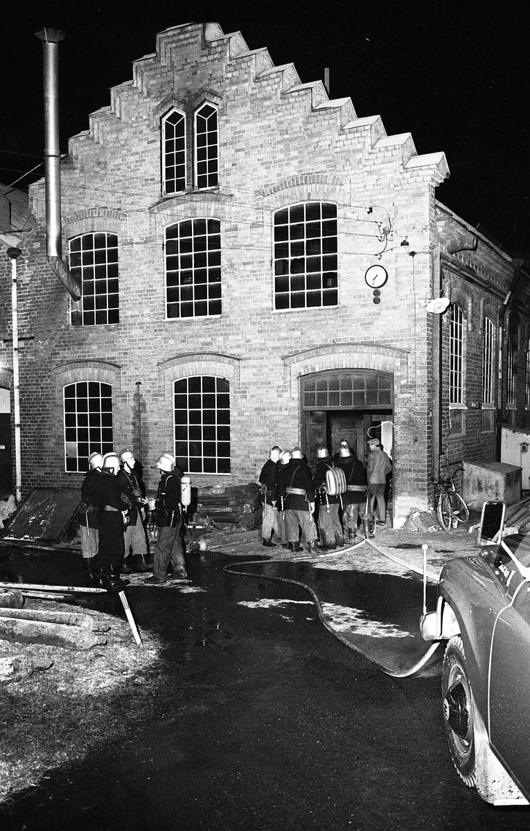 Det brinner i Arboga Margarinfabrik! Flera brandmän, i hjälmar, står utanför byggnaden. Vattenslangar ringlar på marken.