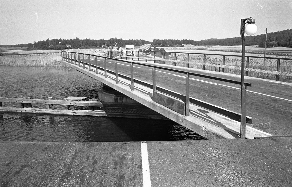 Svängbron över Hjälmare kanal, vid Gravudden, på vägen från Arboga till Kungsör. Människor och bilar i väntan, vid broöppningen.