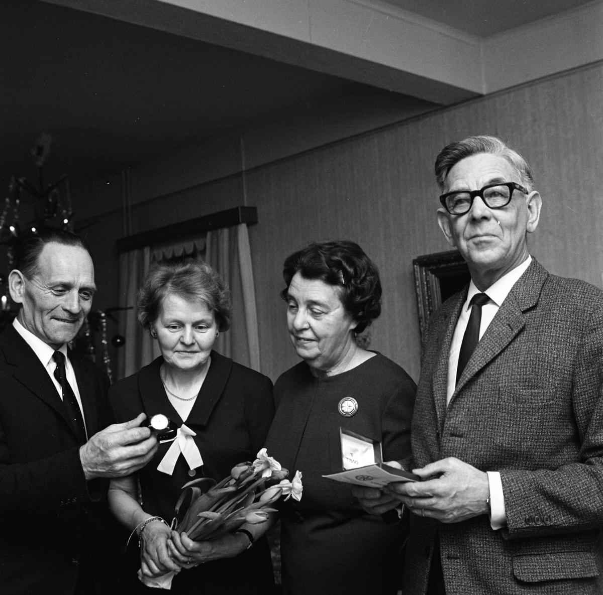 Einar Larsson i Hamre har fått en armbandsklocka. En kvinna håller i en blombukett. Två män och två kvinnor. I bakgrunden anas en julgran.