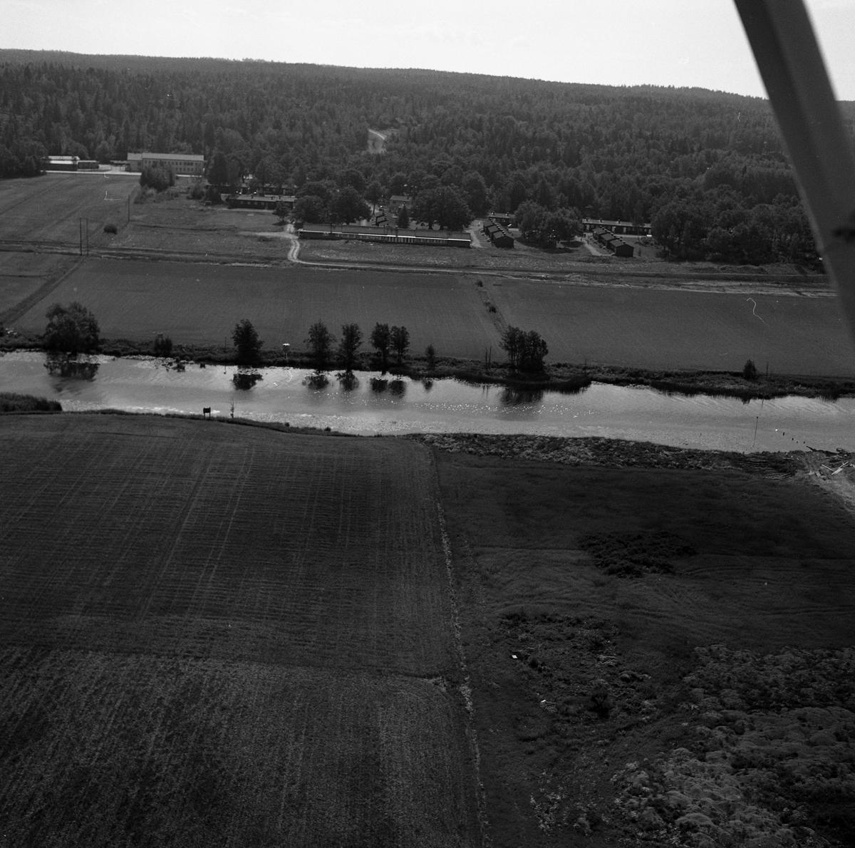 Flygfoto över Ekbacken. Elevhem och bostäder vid Ekvägen. Kungsörsvägen. Arbogaån. Vägen mot Säterbo ses i bildens övre del, i mitten.  Elevhemmet drevs av KFUM på uppdrag av CVA. Startade 1948 och lades ner 1969. Flygbild