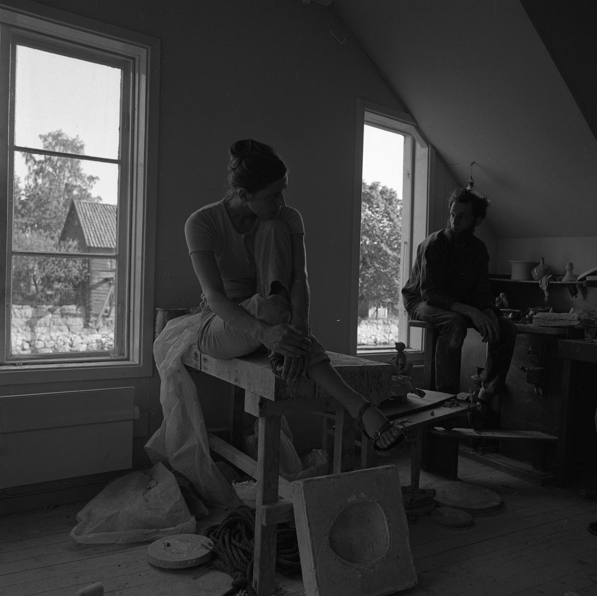 """Keramikerparet Kerstin Hörnlund och Gösta Gräs i ateljén i en ågård. Kerstin sitter på en arbetsbänk. Nedanför henne står en gjutform. Gösta sitter på en hög pall. Bakom honom syns keramikföremål. Läs Kerstins text """"Konstnärsliv i Arboga - möten och minnesbilder"""" i Arboga Minnes årsbok 1998."""