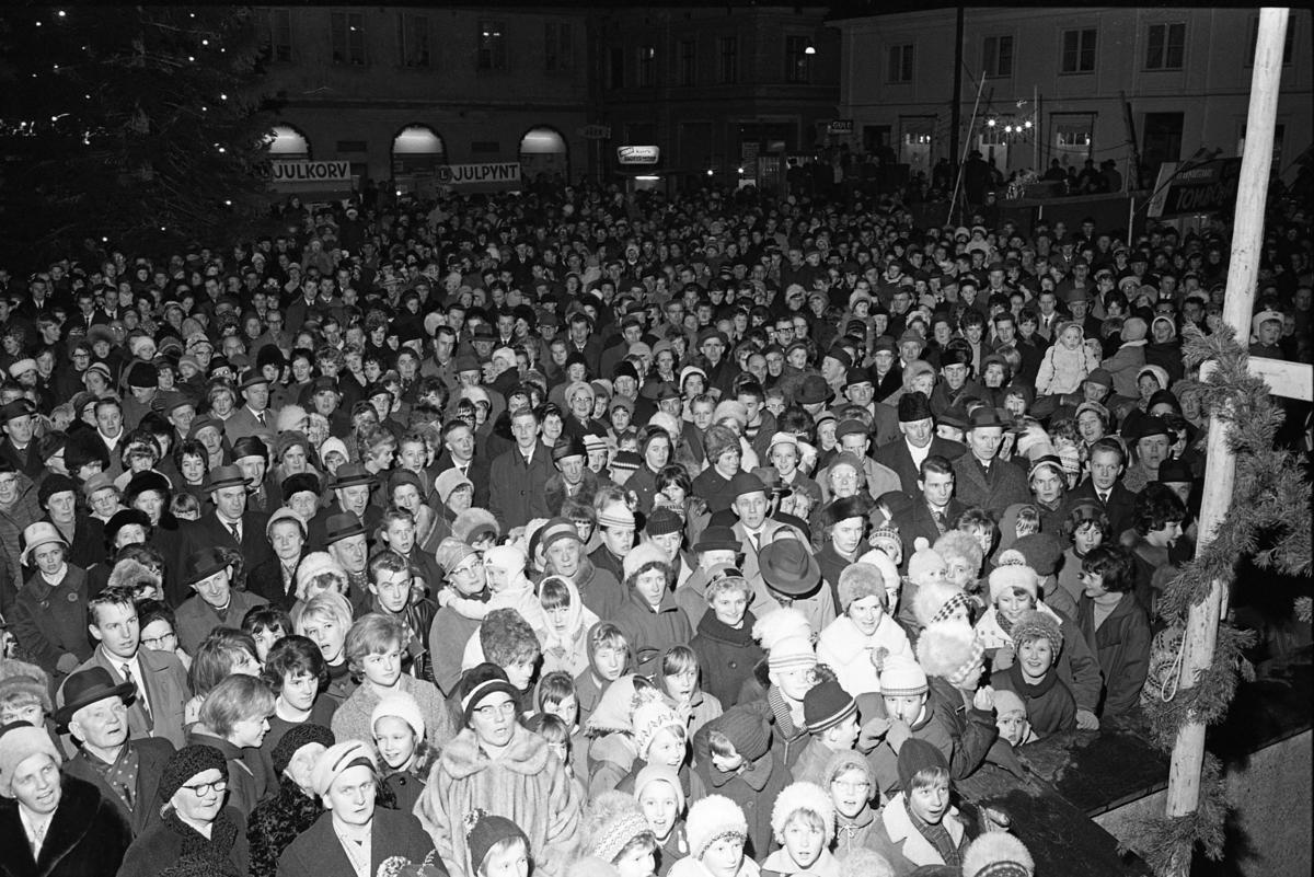 En stor publik är samlad på Stora torget för att se Lucia-kröningen. Scenen står framför rådhuset.