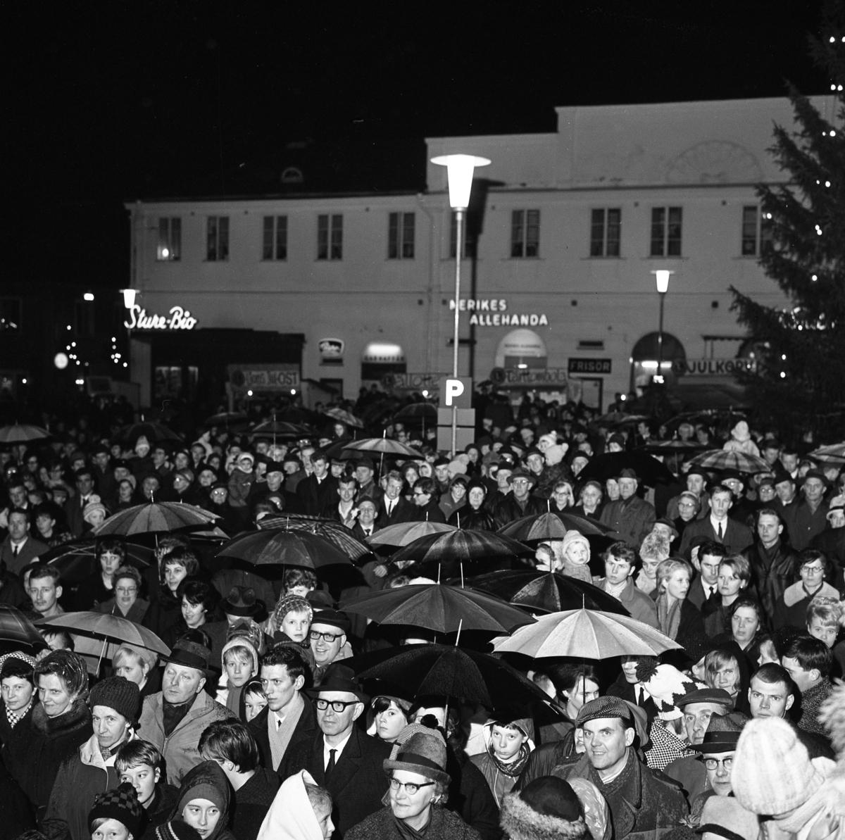 Publiken vid Lucia-kröningen på Stora torget. Många har paraply. Scenen står framför rådhuset. Skyltarna för Sture-Bio, Nerikes Allehanda och Frisör syns i bakgrunden.