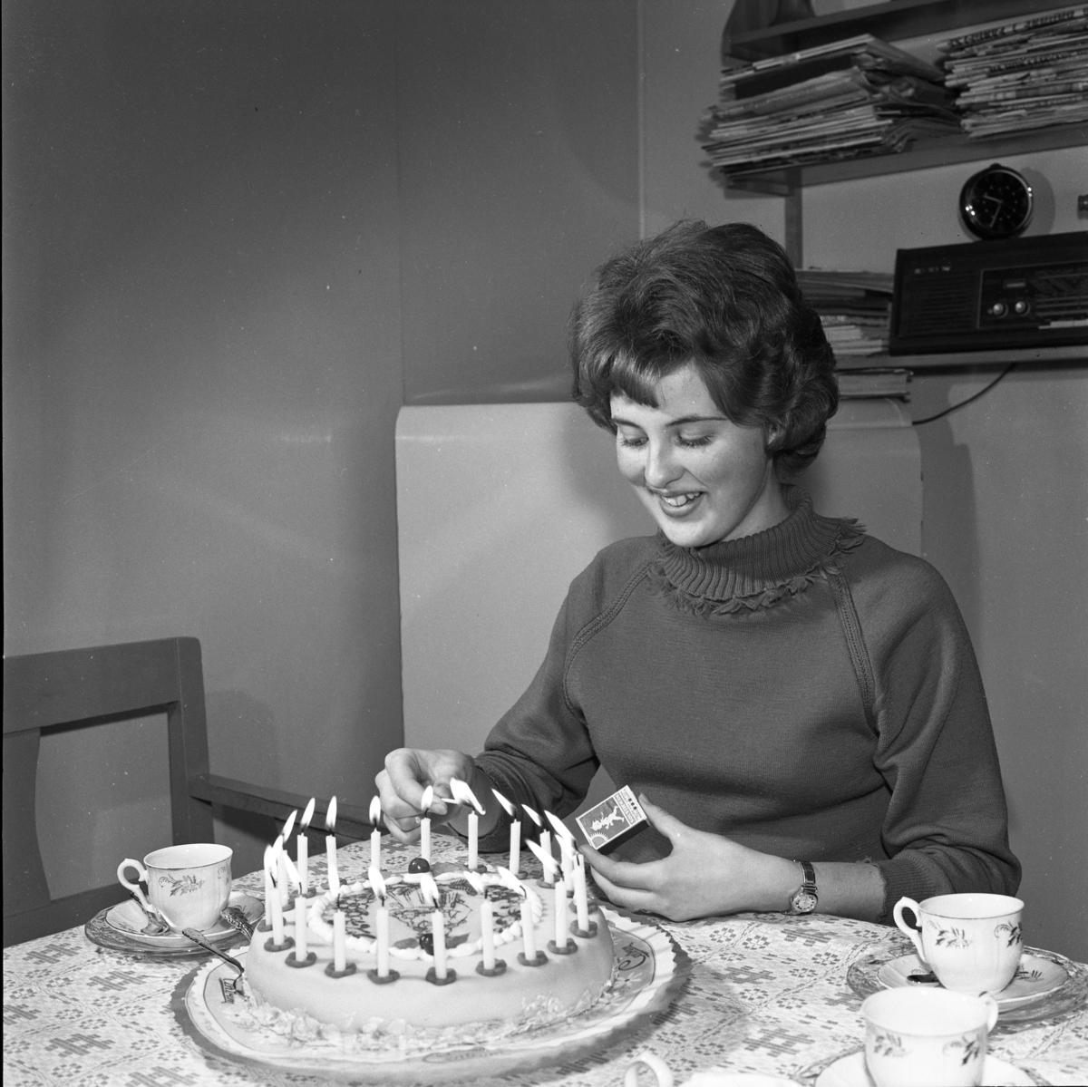 Britt-Marie Gustavsson har valts till årets Lucia. Här firar hon med kaffe och tårta hemma i köket. Bakom hennes rygg står kylskåpet och på en hylla står radion.