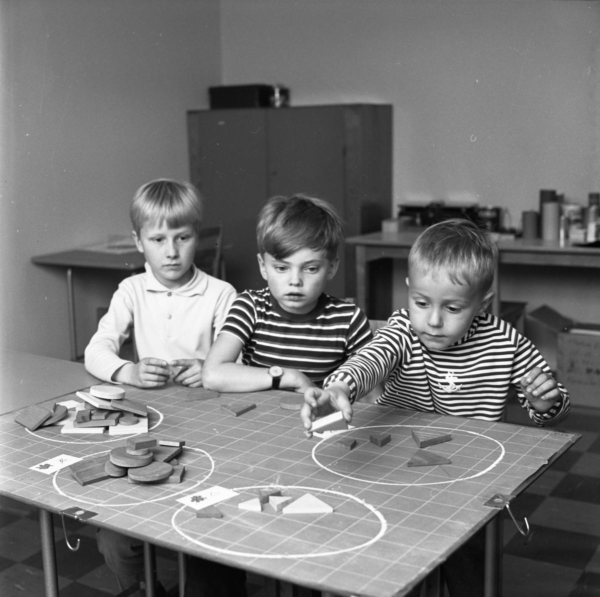 Matematik-klinik Tre pojkar studerar mängdlära i matematiken. Till sin hjälp har de träplattor i olika former.