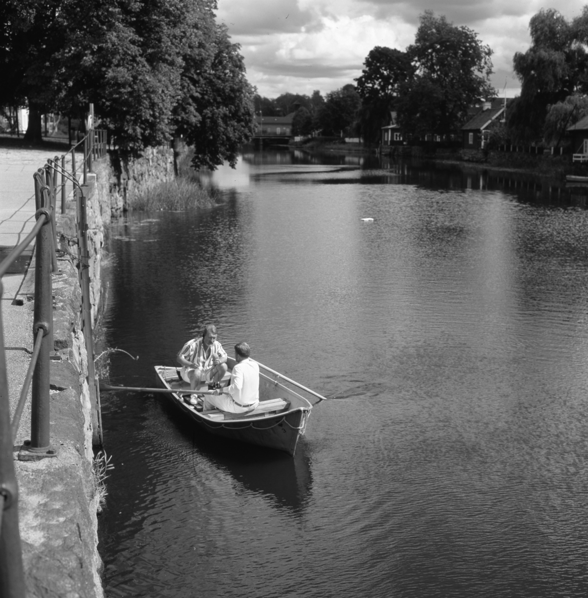 En reporter från Radio Västmanland sitter i en båt på Arbogaån. Han har en mikrofon i handen och intervjuar roddaren. Den mannen är okänd. Båten ligger nedanför Ladbron/Labron/Lastbron